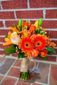 Bright and orange bridal bouquet with gerberas, lilies, alstromerias, roses and hypericum berries