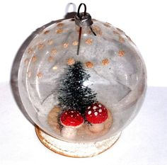 """A WONDERFUL VINTAGE GLASS GLOBE ORNAMENT INSIDE IS A BOTTLE BRUSH TREE & 2 SPUN COTTON MUSHROOMS THIS GREAT ORNAMENT MEASURES APROX. 3"""" TALL & IS IN VERY GOOD VINTAGE CONDITION. THESE ORNAMENTS ARE FROM THE AMAZING COLLECTION OF MARGARET FEIT, MY HUSBANDS MOTHER.MARGARET WAS A CELEBRATED & RESPECTED CHRISTMAS COLLECTOR & KNOWN ON EBAY AS """"MYKIDSTHINKIMCRAZY."""