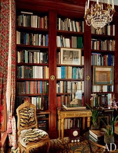 A small space with outsize drama, the library is animated by tiger-stripe carpeting and a gilt-wood chair upholstered in a matching silk velvet by Le Manach from Pierre Frey | archdigest.com