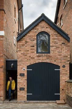 Faux timber doors painted black along with a brick facade help the dwelling blend with its surroundings: the Victorian homes of the Moseley neighborhood in Birmingham UK. Photo by Paul Miller Architecture by by dwellmagazine Brick Shed, Brick Siding, Brick Facade, Architecture Design, Casa Loft, Mews House, Timber Door, Narrow House, Coach House