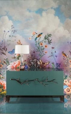 Whimsical cloud and flower wallpaper make a statement with a teal cabinet.