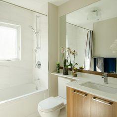 common bathroom upstairs. big mirror, wood cabinets, shelf on top of toilet.