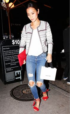 Jamie Chung wears a white t-shirt, distressed skinny jeans, embroidered jacket, and bright red accessories.