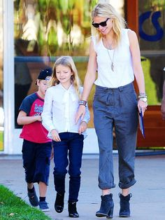Gwyneth Paltrow in a white tank top, gray trousers and boots with daughter Apple son Moses