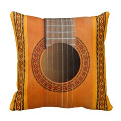 An American Mojo throw pillow or cushion with a photo of a classical guitar in an orange color wood and an inlaid rosette pattern around the sound hole. The pattern design is repeated in vertical stripes on two edges of the pillow. A second more subdued version is available. #guitars #classic #spanish #folk #music #musical #instruments #strings frets