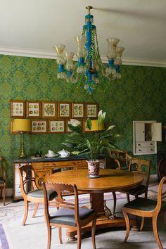 В классической столовой настроение создает традиционная люстра. На фото ее дополняют подобранные в тон обои с активным узором. А мебель здесь самая простая – добротная деревянная классика. Подойдет и антиквариат, и современные реплики.