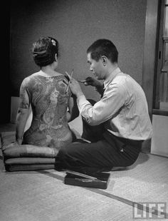 Artist tattooing a gambler's mistress, photographed by Alfred Eisenstaedt, 1946.