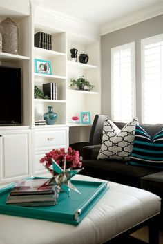 Belmont Design Group Fantastic contemporary family room design with gray walls paint color, espresso microfiber sectional sofa, Windsor Smith Riad fabric pillows, striped turquoise & black pillows, white leather tufted ottoman and white built-ins.