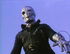 retro-futuristic, robot, mask, helmet, cyborg, prosthetic hand, man in black, sci-fi, humanoid