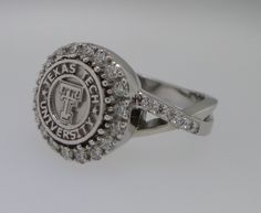 This gorgeous Texas Tech class ring features a diamond halo around a 9mm coin with a delicate crossover shank to create a stunning look. Shown in white gold. Also available in yellow or rose gold.