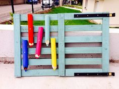 A pallet made into a gate. It is painted and trimmed out with added pickets pointed and painted to look like colored pencils.