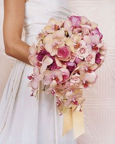 Buttercream-and-pink phalaenopsis orchids flutter like butterflies among ruffle-edged, magenta garden roses, pale-pink rounded garden roses, and still paler spray roses. The tails of a light yellow ribbon emphasize the bouquet's downward sweep.    Read more at Marthastewartweddings.com: A Shower of Flowers Rose Bouquet