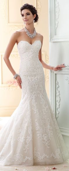This elegant A-line vintage wedding dress features a scalloped sweetheart neckline, back covered buttons down to hem, with a chapel length train
