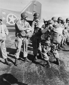 W.W. II, c.1942, U.S. paratroopers inspecting parachutes before taking off on maneuvers in England.