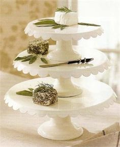 "Enamel Cake Stands   available in three sizes     As Seen in Country Living  These attractive enamel cake stands, with scalloped edges, are perfect for displaying your creative creations. Use them separately or layer as shown. Great for cheese, cookies, cakes and more. Entertain with these elegant enamel cake stands. Antique White. Small 3.25""H x 8"" Diam; Medium 4.25""H x 10"" Diam; Large 4.75""H x 12"" Diam.  Price: $24.95"