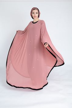 Crafted from a layer of chiffon and delicately studded with pink pearls, this batwing abaya cascade into a romantic notion. Made in the UAE. Street Hijab Fashion, Abaya Fashion, Fashion Dresses, Disney Wedding Dresses, Pakistani Wedding Dresses, Wedding Hijab, Modest Dresses, Plus Size Dresses, Modern Abaya