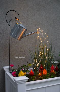 Glowing Watering Can with Fairy Lights - How neat is this? It's SO EASY to make! Hanging watering can with lights that look like it is pouring water.