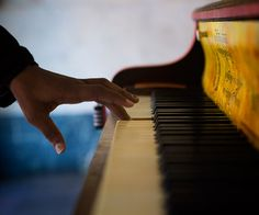 Play Me, I'm Yours | A curious Medina Phillips, 22, plays the piano outside the Strand Theater. (Jesse Costa/WBUR)