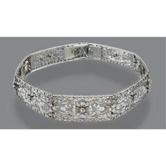 A diamond belle epoque bandeau which also doubles as a bracelet. Designed as seven open-work diamond panels, with a central floral motif.