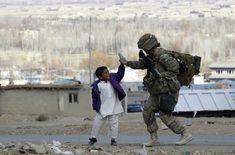 Un enfant afghan tape la main d'un soldat américain.