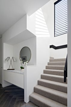 Entry details This modern hallway has a floating built-in cabinet, with a light colored carpeted staircase and a black railing that leads to the upper floor, with a matching black window frame. Modern Hallway, Modern Stairs, Black Window Frames, Carpet Staircase, Escalier Design, Hallway Carpet Runners, Stair Runners, Carpet Decor, Interior Stairs