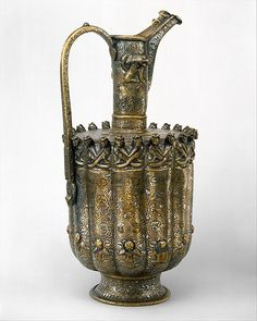 Ewer. Date: ca. 1180–1210. Geography: Iran, Khurasan. Culture: Islamic. Medium: Brass; raised, repoussé, inlaid with silver and black compound. Dimensions: H. 15 3/4 in. (40 cm) Diam 7 1/2 in. (19.1 cm). Accession Number: 44.15. On this ewer, each Zodiac symbol is shown with its Planetary Lord.