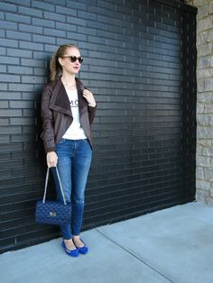 graphic sweatshirt, brown leather jacket, distressed skinny jeans, cobalt suede flats, navy quilted bag