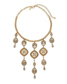 Matte gold-tone necklace fringed with intricate pendants ablaze with crystals.