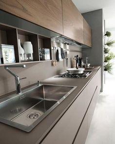 Nessa cozinha o revestimento da parede da pia, do armário posterior, assim como o da superfície da pia é o mesmo, esbanjando elegância e também valorizando os armários superiores - com portas de madeira - e os eletrodomésticos.
