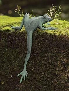 On the edge of a step or shelf, this climbing frog is headed for mischief. It is crafted of aluminum with a verdigris finish.
