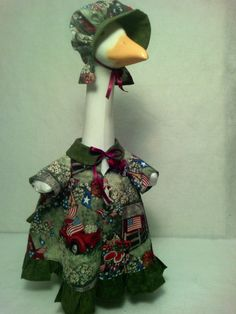 A Summer time fun lawn goose dress. Print on cotton fabric consist of an old time Red Pickup Truck, Red Barn, Flags, USA, Watermelons, Apples, and Dogs, printed on a green grass background. To complete her outfit, she has a cotton green ruffle around bottom of dress, a matching green collar, and brim on bonnet. She is ready for a summer time picnic.  Outfit will fit a plastic or concrete lawn goose measuring 23 - 25 goose.  All my items are handmade by me and are one of a kind. This piece…
