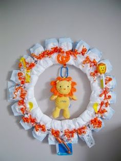 Diaper wreath as a decoration for the baby shower. I'm going to try to make this by bending a metal clothes hanger into a circle, and I'll wrap diapers around it and secure each with ribbon.