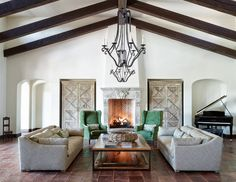 Mediterranean living room with cathedral ceilings, beams, terracotta floor tile and wrought iron lighting.   mediterranean-style-living-room-with-terracotta-floor-tile-cathedral-ceilings-dark-stained-ceiling-beams-and-wrought-iron-lighting-the-refined-group