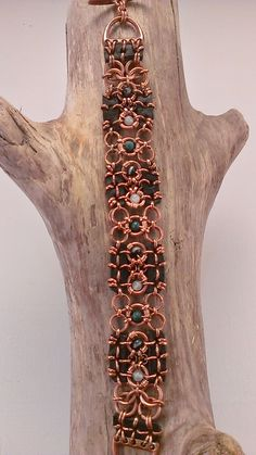 This untreated copper chainmaille and leather bracelet has polished gemstone…
