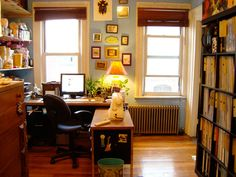 there's something about this home office i like, despite the fact that i could never ever handle wonky picture frames on the wall and that much clutter. (see bookshelf to the left.)  nonetheless, as someone with small rooms upstairs and a house with two teachers with lots of books and files, this remains an inspiration of sorts.
