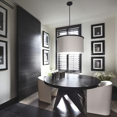 Dining Room Designs | Contemporary design with a black round table and white chairs. In a room with a black wood panel that creates an amazing sense of design | Visit us at http://moderndiningtables.net/ | #kellyhoppen #modernfurniture #moderndesign #interiordesign #moderndiningtable #diningtable #diningroomsets #minimalistdesign #contemporarydesign #whitedesign #whitechairs #roundtable #simpledesign #woodwall
