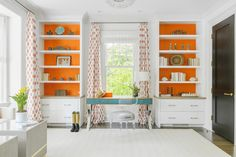 White drawers are fitted beneath styed white built-in bookshelves accented with orange backs and fitted on either side of a window dressed in white roman shades layered behind white and orange curtains. Blue Home Offices, Orange Office, Orange Curtains, Blue Shelves, Interior Design Masters, Shingle Style Homes, Orange Wallpaper, Orange House, Elegant Kitchens