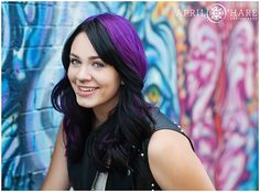 A gorgeous high school senior punk rock styled girl with black and purple hair poses in front of a graffiti street art wall in the Santa Fe Art District neighborhood of downtown Denver, Colorado