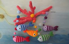 Brightly colored fish hanging from coral - a crochet mobile that is perfect for your baby's nursery (or for any room in the house).