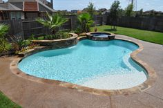 Free form swimming pool and spa in Katy, TX (Houston, TX) features raised spa, tiered flagstone spillway, raised wall planter faced in Ledger Stone (by NPT) with sheer descent waterfall, tanning ledge with bubbler fountain, plaster interior in pool, glass bead interior in the spa, chocolate acrylic deck, drains, and tropical landscape package, all by Redman Pools, Inc. Houston, Tx Pool Builder, www.redmanpools.com