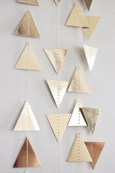 Paper garlands add a little whimsy to any party or everyday home decor. - 2 inch triangles - Sewn together with metallic gold thread - Double sided Gold Foil Custom color and lengths are always welcomed (see last photo for other speciality paper options...regular card stock colors