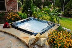Nice use of greenery, flowers, and an in-ground spa installation to make the hot tub fit into the landscape perfectly. Well done.