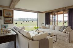 Designed by Kathleen Walsh, the palette for this Martha's Vineyard living room was kept neutral to let the views be the central focus. From the outside, the crystal-clear picture window resembles a flung-open barn door.