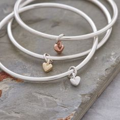 A sterling silver bangle with solid gold heart charm from award winning designer Scarlett Jewellery - made in the UK, gift boxed with free UK delivery. www.1planet7billionworlds.com