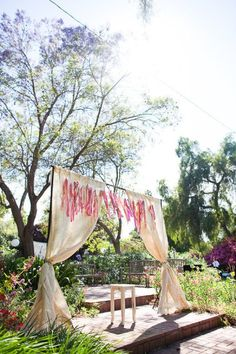 Set the stage with tall curtains in a neutral shade; then hang a ribbon garland that goes with your color palette. Photo by Mr. Haack via Style Me Pretty