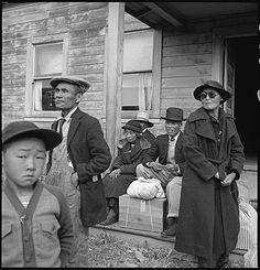 May 9, 1942: Centerville, California. Farm families of Japanese ancestry awaiting the evacuation buses which will take them to the Tanforan Assembly center along with 595 others evacuated from this district under Civilian Exclusion Order. Dorothea Lange, photographer. From the Central Photographic File of the War Relocation Authority