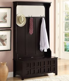 This hall tree features a mirror at the top, coat hooks and a storage bench base.