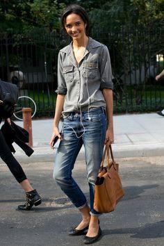 Model Cora #Emmanuel in #gray button-down, faded #jeans, black flats, camel bag