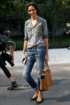 Model Cora #Emmanuel in #gray button-down, faded #jeans, black flats, camel bag