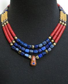 by Luda Hunter | A vintage Kiffa (Mauritania) bead sits at the center of this triple strand necklace. It has been combined with Lapis barrels at the front of the necklace with five rare Tuareg gold wash brass cornerless beads from Mali. Red Vulcanite heishi beads from the Africa Trade period, antique yellow flower beads also from African trade with Nigerian brass beads and silver daisy spacers beads. | 311$